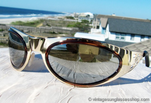 c0870547b45 VS2964  Vintage Killer Loop K0272 Venom sunglasses date to the brand s  ownership by Bausch   Lomb and feature a gleaming gold wrap style frame  that contours ...