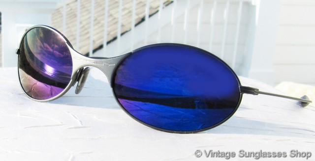 vs1899 vintage first generation oakley e wire steel gray blue iridium sunglasses feature a cool steel gray frame and rare oakley blue iridium lenses