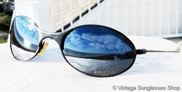 c50ba8f000 VS1900  Vintage first generation Oakley E Wire Titanium sunglasses feature  a gleaming black frame and Oakley Chrome Iridium lenses