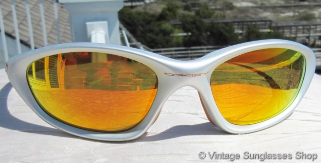 05c86ba94fb VS2647  Vintage Oakley XX sunglasses feature a cool silver frame with orange  highlights