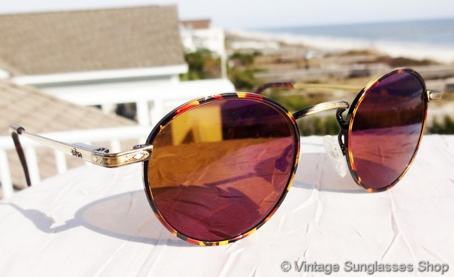 20ee4bdda279 VS021  Vintage Revo 1105 008 sunglasses combine an antique gold frame with  Revo s amber and purple lenses surrounded by a thin band of tortoise shell